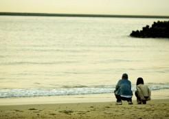 砂浜にすわるカップル