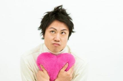 ピンクのハートのクッションを抱きかかえる男性