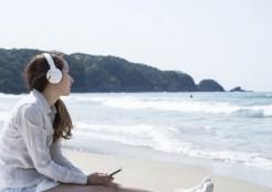 砂浜で一人音楽を聴く女性